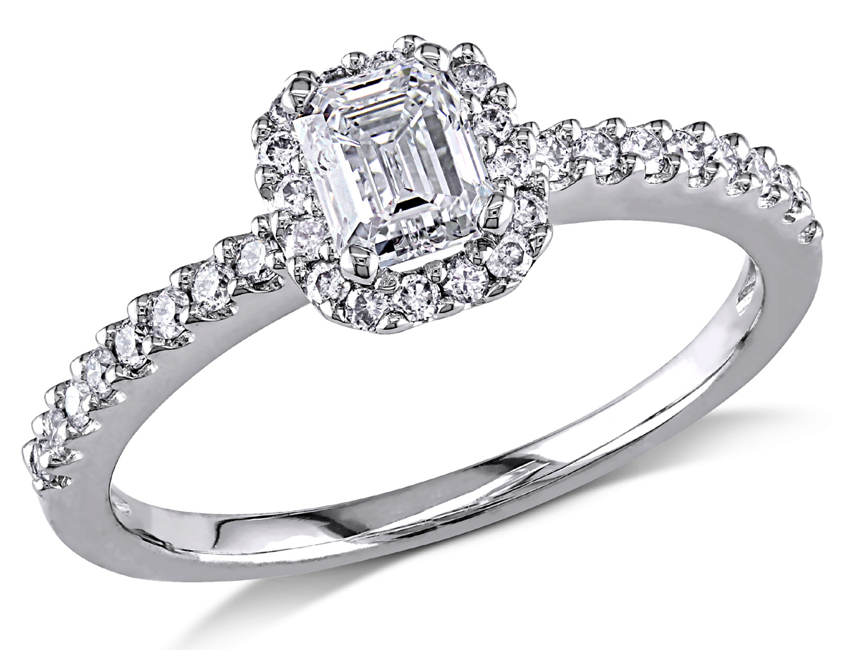 This beautiful ring features an emerald-cut diamond center stone with accenting round diamonds set in 14 karat white gold. The ring glimmers with a highly polished finish.
