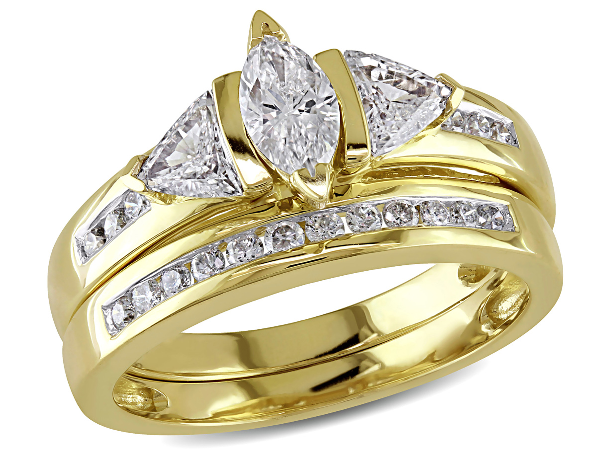 This stunning bridal ring set features a marquise-cut diamond center stone with diamond side stones set in 14 karat yellow gold. Ring glimmer with highly polished finish.