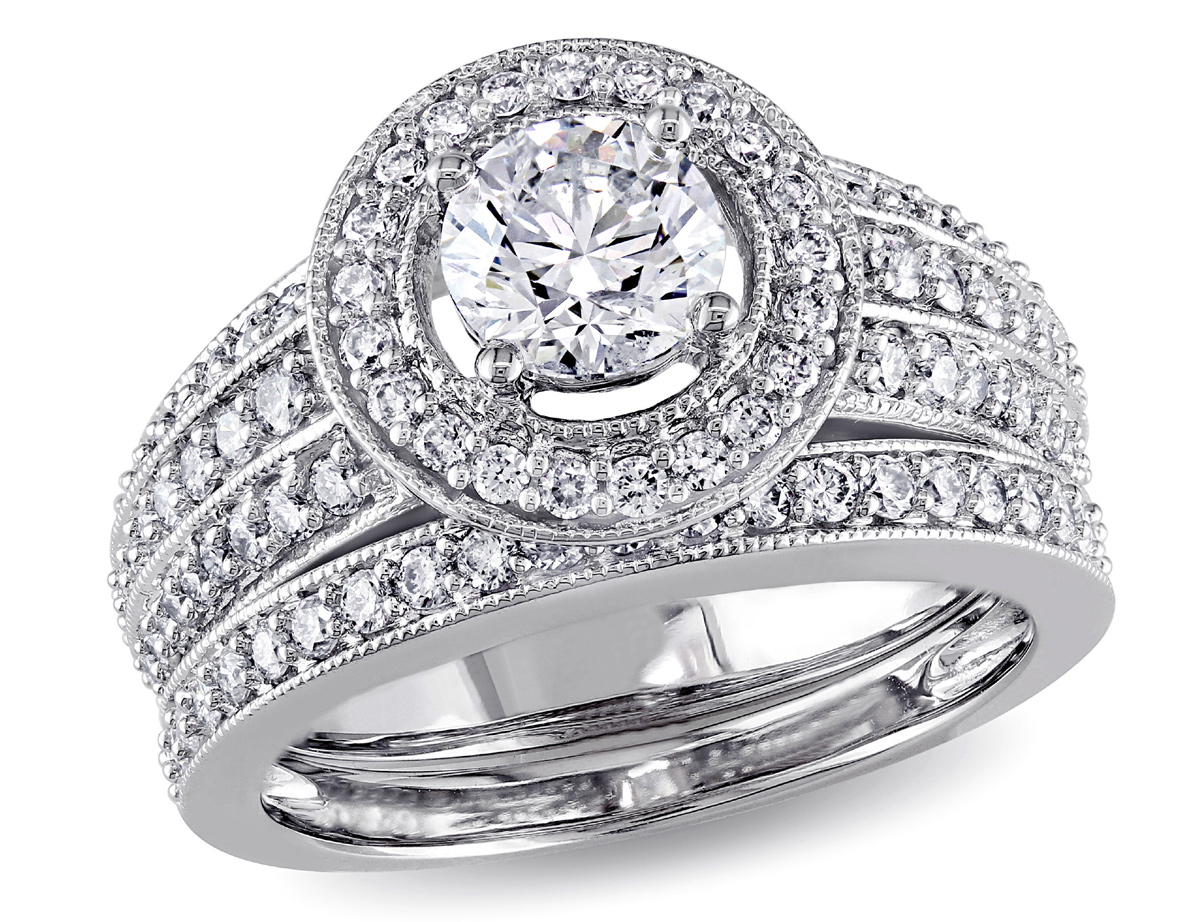This exquisite one-of-a-kind bridal set features a gorgeous engagement ring with a round-cut white diamond center stone surrounded by a halo of scintillating diamonds. This brilliant ring is complemented by a stunning eternity band. The rings are crafted of gleaming 14-karat white gold enhanced with a miligrain finish.