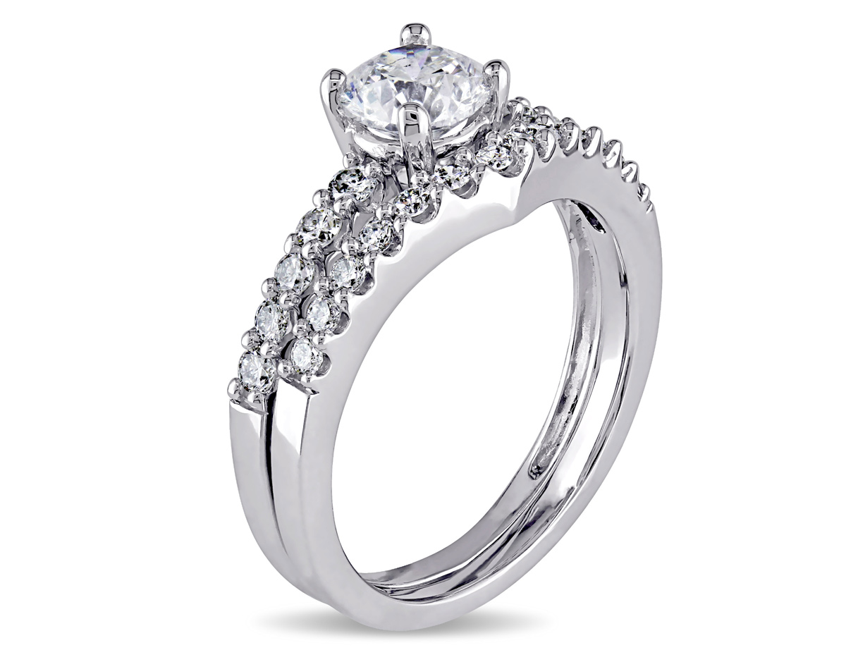 This exquisite bridal ring set features a stunning engagement ring with a contour wedding band set in 14-karat white gold. These gorgeous rings are enhanced with a high polish finish.